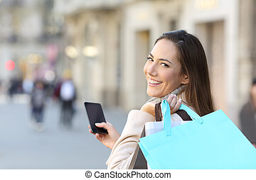 Happy shopper holding phone and shopping bags