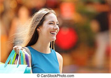 Happy shopper with shopping bags walking