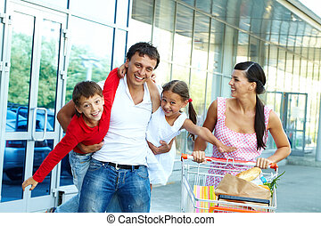 Happy shoppers - Portrait of happy family of four with cart ...