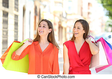 Happy shoppers walking in an old town holding shopping bags