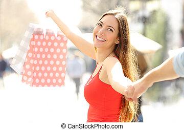 Happy shoppers walking showing shopping bag