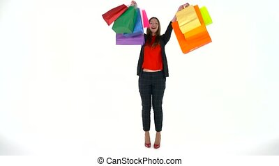 Female shopper holding multicolored shopping bags on white...