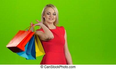 Happy shopping woman makes selfie on mobile, green screen studio