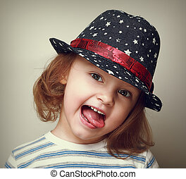 Happy showing the tongue kid girl in fashion hat. Closeup...