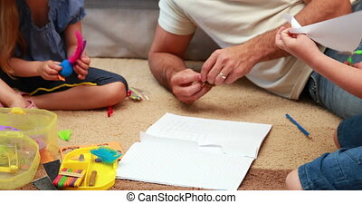Happy siblings doing arts and crafts on the rug with parents...