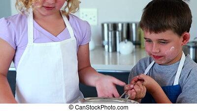 Happy siblings making a cake togeth