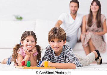 Happy siblings playing board game on floor