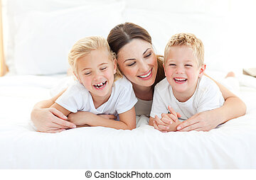 Happy siblings playing with their mother lying on a bed