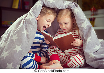 Happy siblings reading book under cover