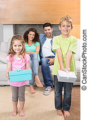 Happy siblings showing presents in front of parents on the couch at home in living room