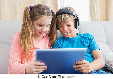 Happy siblings using tablet pc on sofa