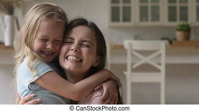 Happy single mom hugging cute little kid daughter laughing bonding