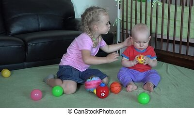 happy sister kiss her little brother playing with colorful balls at home