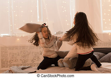 Happy sisters are playing in their room. Cute little girls fight pillows in a room in the evening dim light