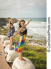 Happy sisters playing in the shore next to beach