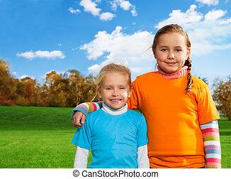 Happy sisters walking in park