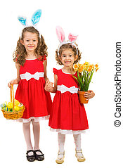 Happy sisters with bunny ears and easter eggs