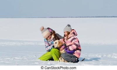 Happy sisters with cute dog on winter walk