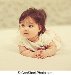 Happy six months old baby girl lying on blanket