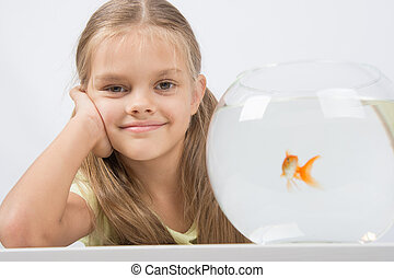 Happy six year old girl with an aquarium and a goldfish