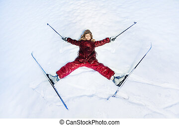 Happy skier laying as a star on the snow