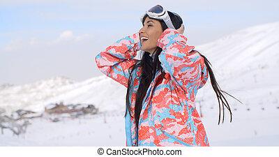 Happy skier pulling back hair