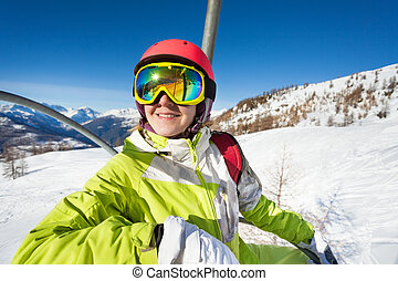 Happy skier riding to top of mountain on chairlift