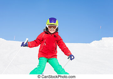 Happy skier walking down the hill in mountains