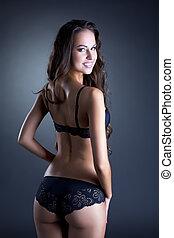 Happy slim brunette advertises erotic lingerie, on gray...