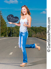 Happy slim girl hitchhiking on the asphalt road