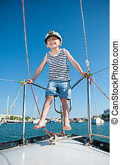 happy small boy wearing captain cap on luxury white yacht in...