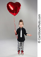 Happy small boy with red heart balloon on a light background