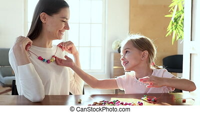 Happy small child daughter making necklace for young mom - ...