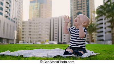 Happy small child sitting in grass with white daisies city...