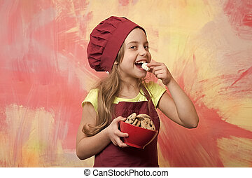 happy small girl eating chocolate cookies dessert in cook hat