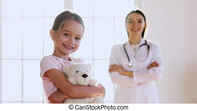 Happy small girl holding toy with female pediatrician on background.
