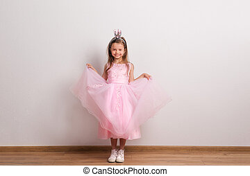 Happy small princess girl with crown headband in studio on a white background.