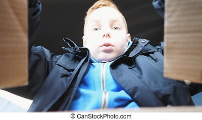 Happy small red-haired boy opens cardboard box and pulls out gift from it sitting in a car. Little male child looks inside of package shows surprise and joy on his face. Low view Slow motion