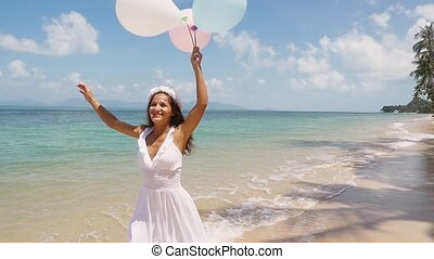 Happy smiles pretty bride running on the beach on tropical island, holds balloons in hand. slow motion. Concept happiness, freedom, vacation, love. 1920x1080