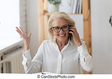 Happy smiling 60 years old businesswoman talking on phone.