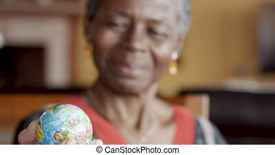 Happy smiling African American mature woman over 50 looking a world globe
