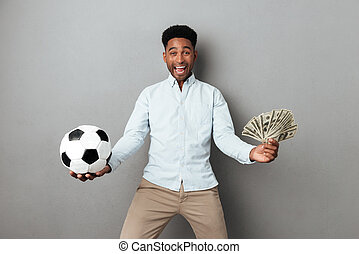 Happy smiling african man holding football and money