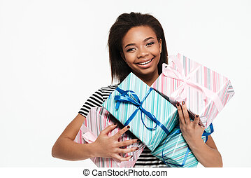 Happy smiling african woman holding stack of present boxes