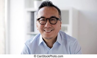 happy smiling asian businessman at office