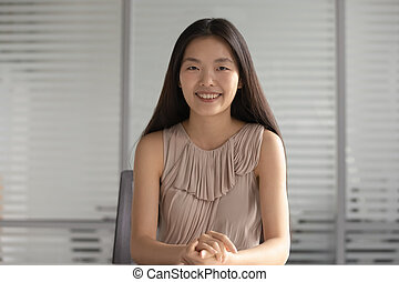 Happy smiling asian businesswoman looking at camera sit at desk