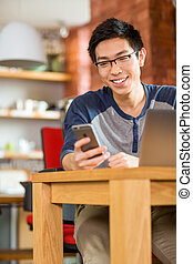 Happy smiling asian student using laptop and cellphone