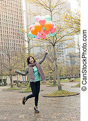 Happy smiling Asian woman holding balloons