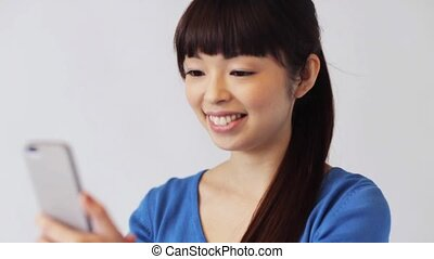 happy smiling asian woman with smartphone