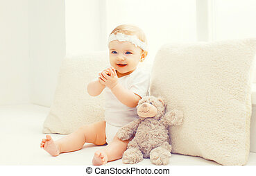 Happy smiling baby playing at home in white room near window