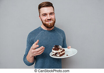 Happy smiling bearded man eating chocolate cake isolated on...